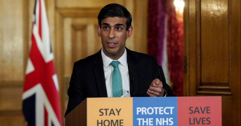 "Rishi Sunak behind podium with the words, ""Stay home, protect the NHS, Save Lives"" on the front"