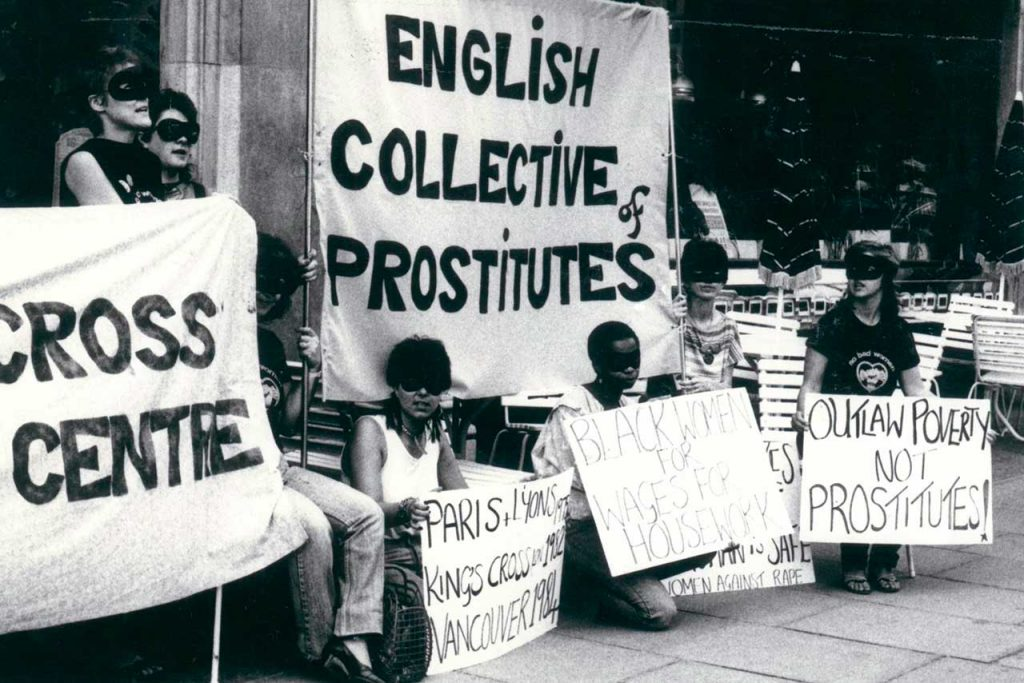 Black and white photo of a English Collective of Prostitutes banner with people stood and kneeling with signs